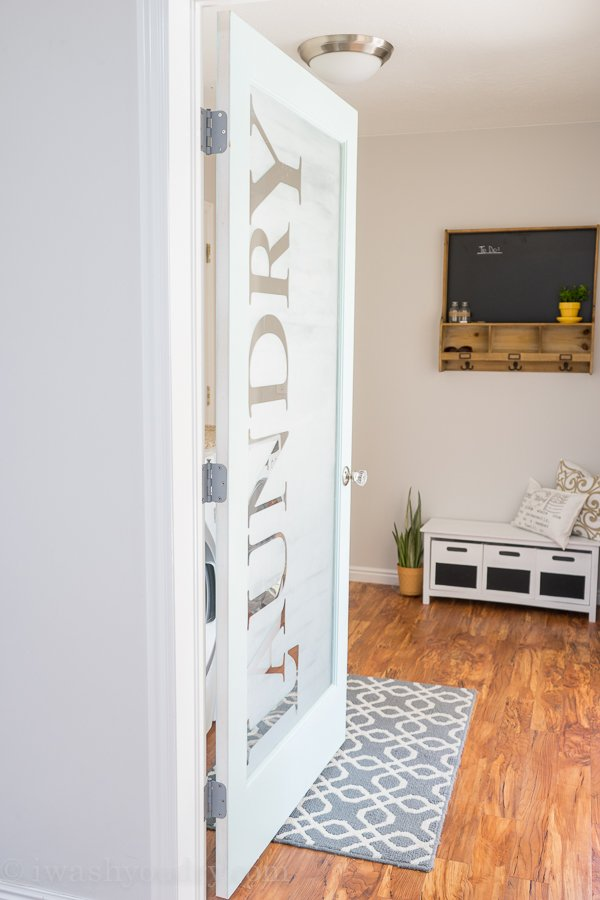 LOVE this Laundry Room door! She uses vinyl letters then frosted the glass for privacy, yet still lets in a lot of natural light. The rest of the kitchen reveal is just as awesome!